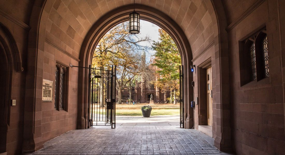 View of the gates at the end of an outdoor arched corridor looking out on to a green with distant people congregated on it.