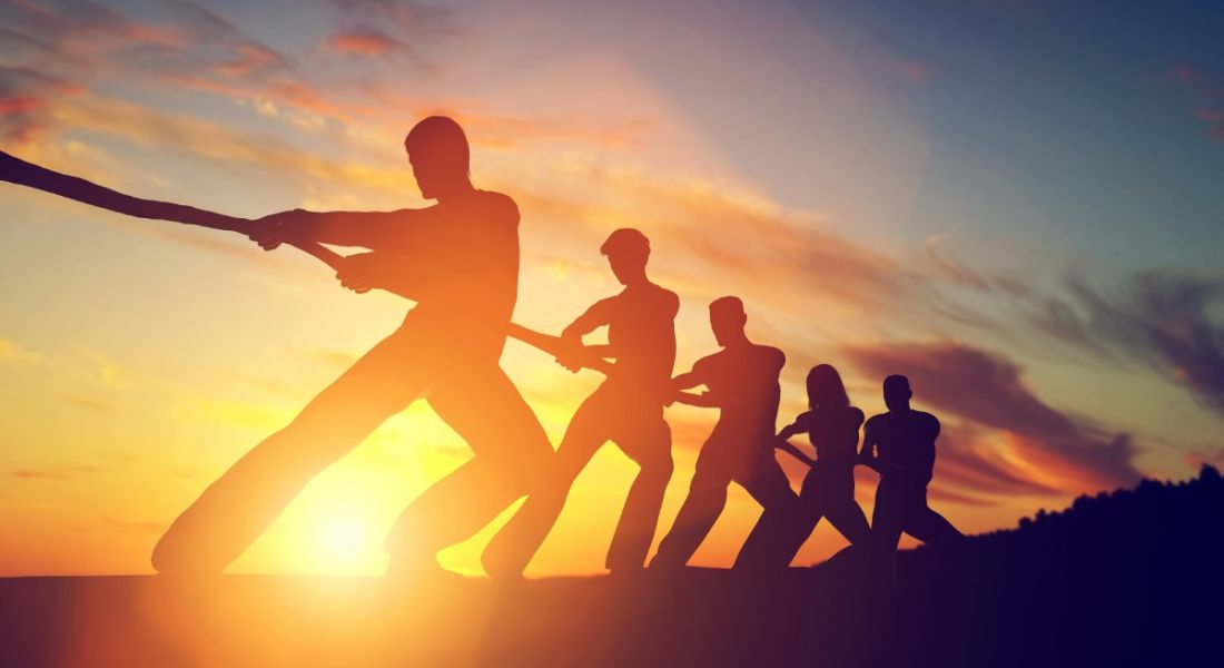 A silhouette of several people playing tug-o-war against a sunset. This depicts the financial industry battling for talent.
