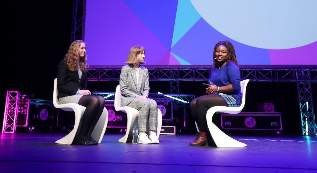 Three young women sitting in chairs on a stage at Inspirefest. They are discussing life for women in STEM.