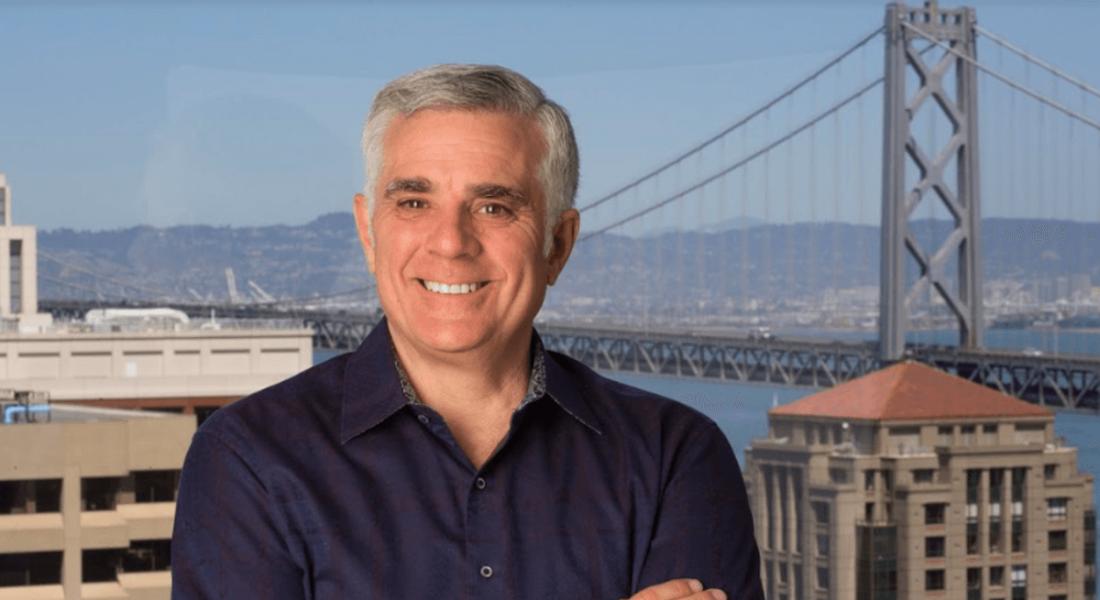 Man in dark shirt standing before an image of the Golden Gate bridge.