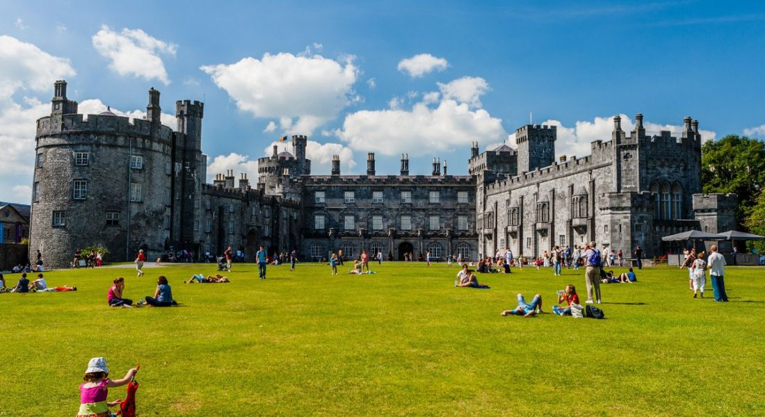 People sitting and playing on the grass in front of Kilkenny castle on a summer day under a blue sky.