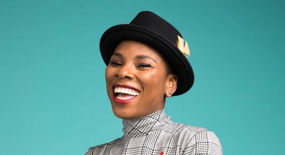 A close-up headshot of a smiling woman wearing a black hat against a bright turquoise background. She is Luvvie Ajayi.
