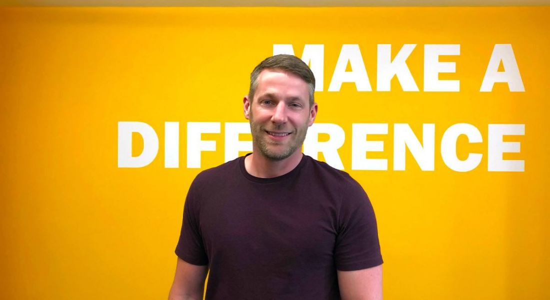 A man with fair hair wearing a dark red t-shirt smiling in front of a yellow wall that says make a difference.