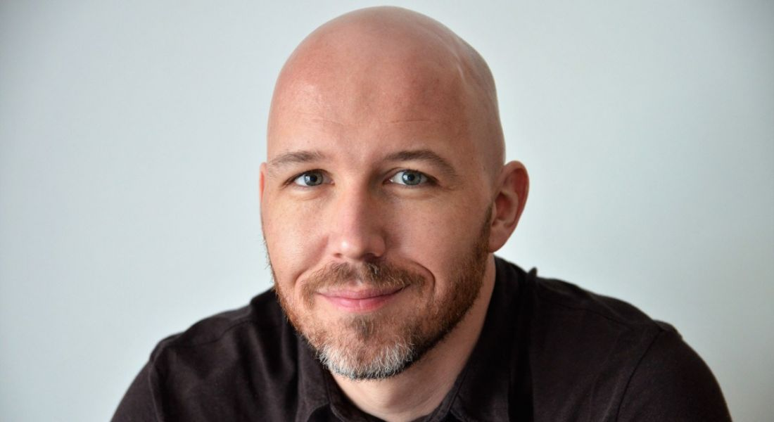 A close-up headshot of a bald man with stubble wearing a dark t-shirt. Here, he talks about paternity leave.