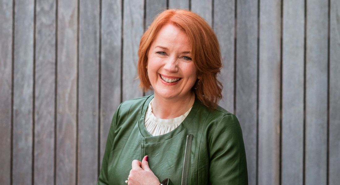 A woman with short red hair wearing a green jacket standing in front of a wooden fence.