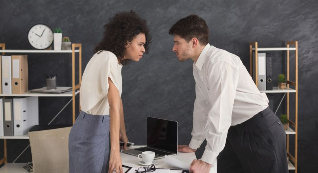 A male and female employee at logger heads lean into each other over an office desk with angry expressions.