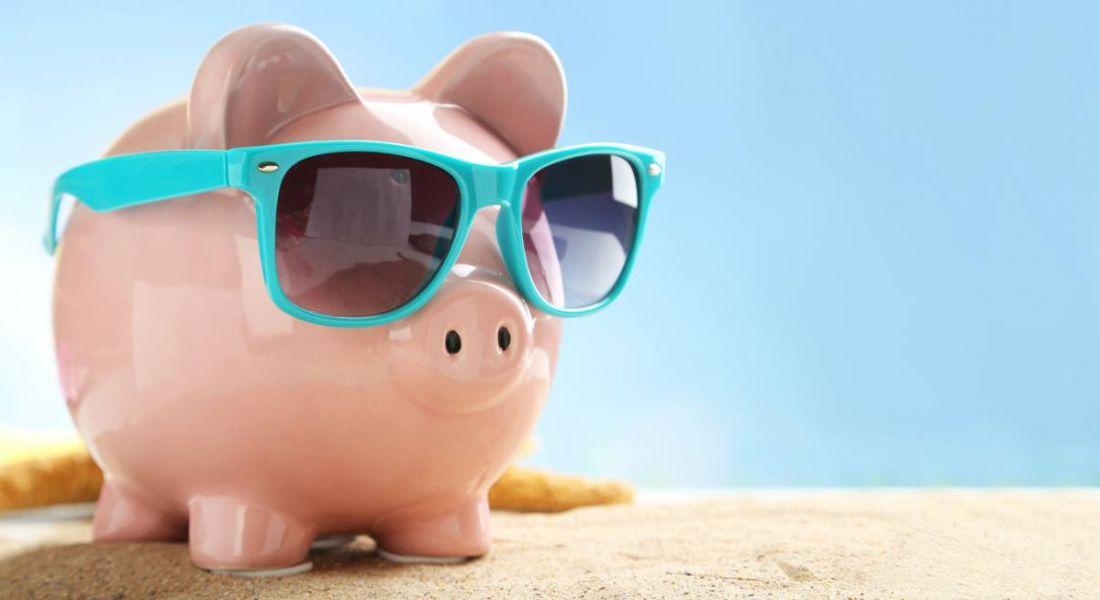 A pink piggy bank on a sandy beach in the sunshine with sunglasses. He is depicting hot jobs in fintech.