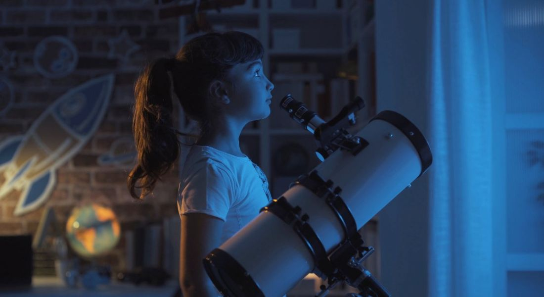Young girl stargazing at night beside a telescope in a room with a globe and space decorations on the wall.