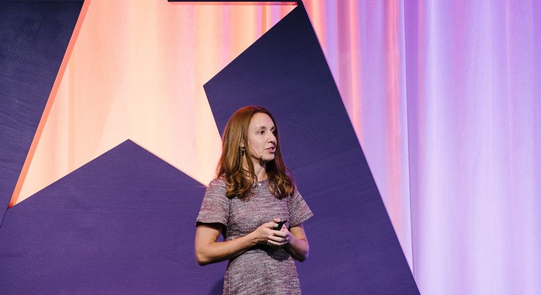 A woman with brown hair standing on a stage, giving a talk. There is a purple wall behind her.