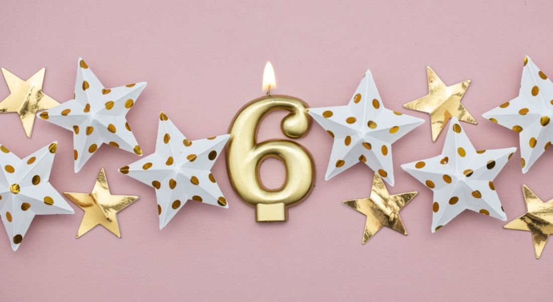 A gold number six candle on a pink background surrounded by decorative stars. It represents six fintech myths.