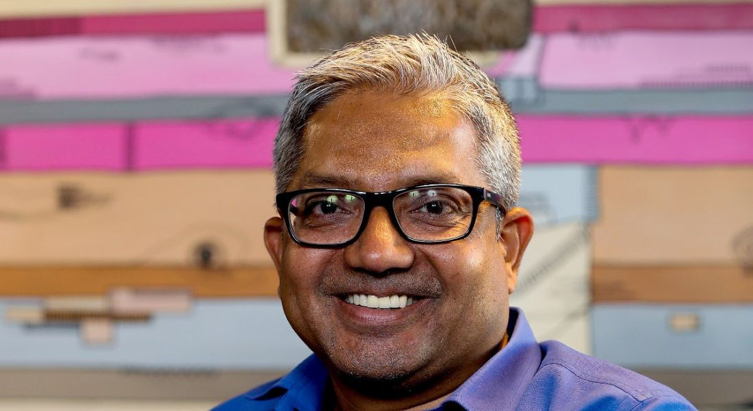 Smiling man with glasses wearing blue shirt and looking at camera, against striped backdrop.