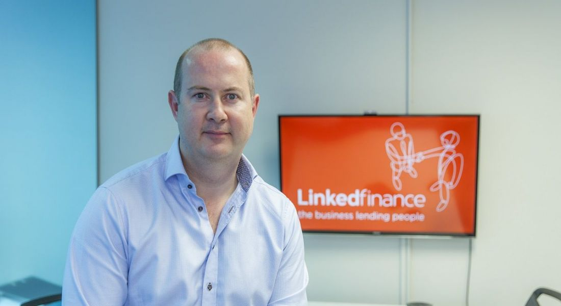 Niall Dorrian in a light blue shirt sitting on a desk with a Linked Finance logo behind him.