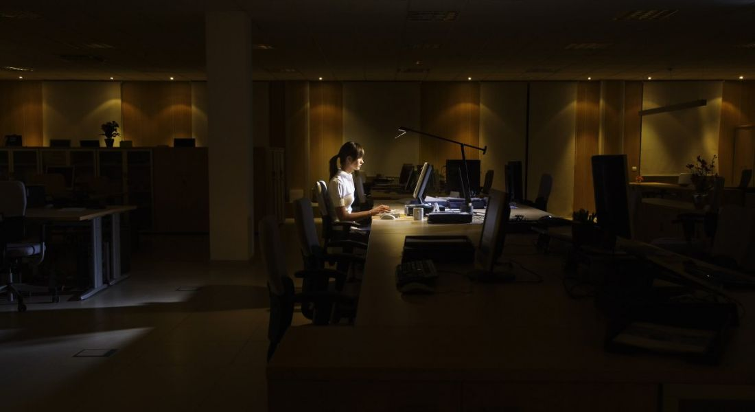 Side view of a young woman working on computer in dark office.