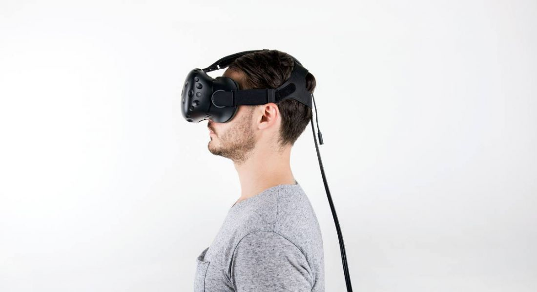 Profile view of a man in a grey T-shirt wearing a virtual reality headset.