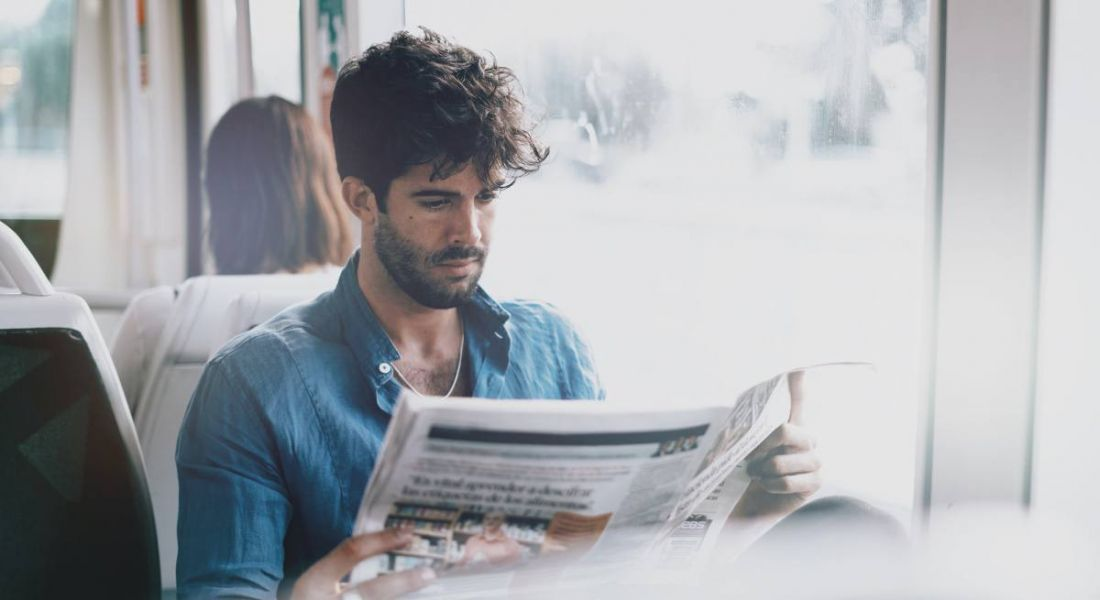 Man sitting next to window reading newspaper and looking for new job.
