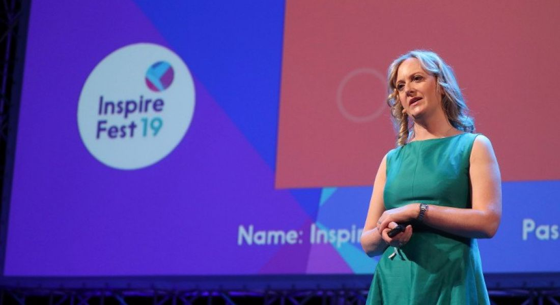 Woman in green dress with blonde hair standing on the Inspirefest 2019 stage.