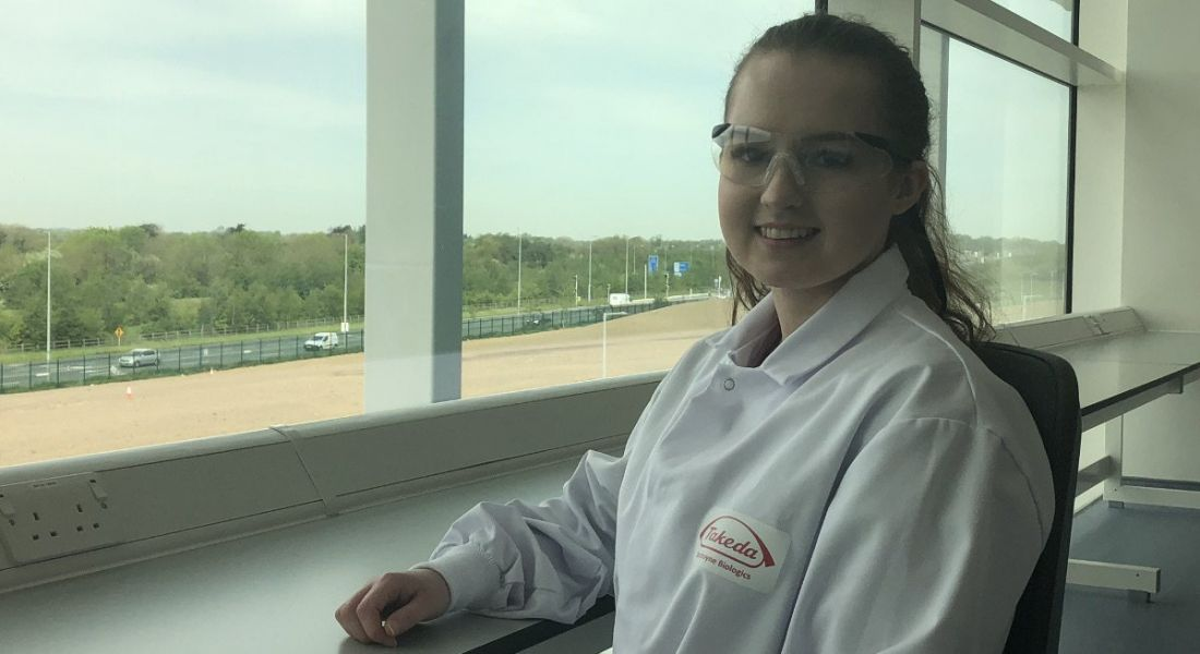View of young woman wearing safety goggles and lab coat with Takeda logo on it sitting beside a large window.