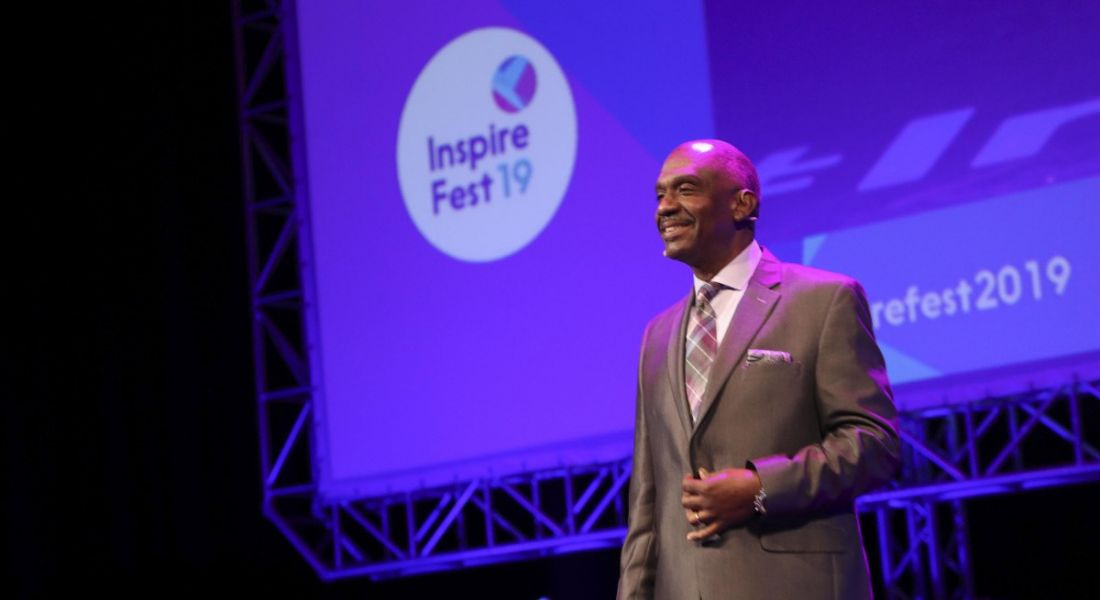 A man in a slate grey suit grinning widely at a crowd at the Inspirefest 2019 conference.