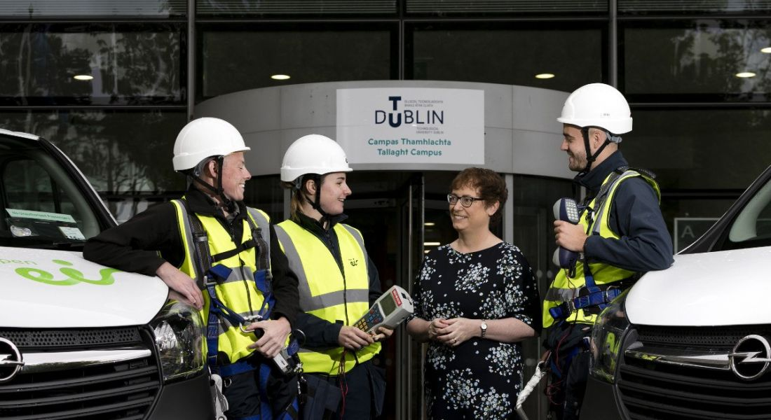 Group of Eir apprentices in hard hats and high-vis gear laughing and chatting with a woman with brown cropped hair and glasses.