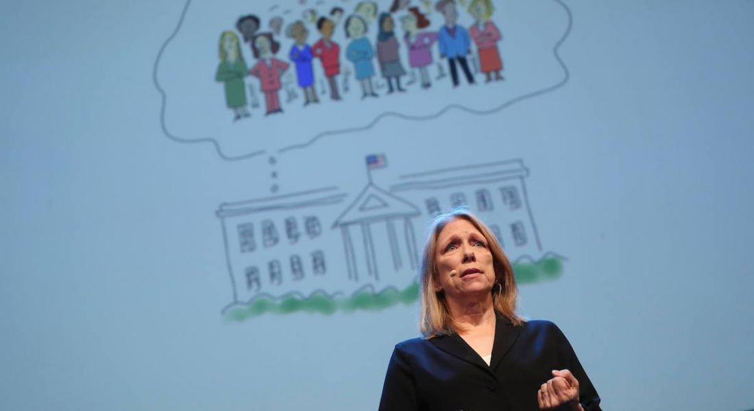 blonde middle aged woman in black speaking on stage in front of cartoon sketch of the White House with women in thought bubble above it.