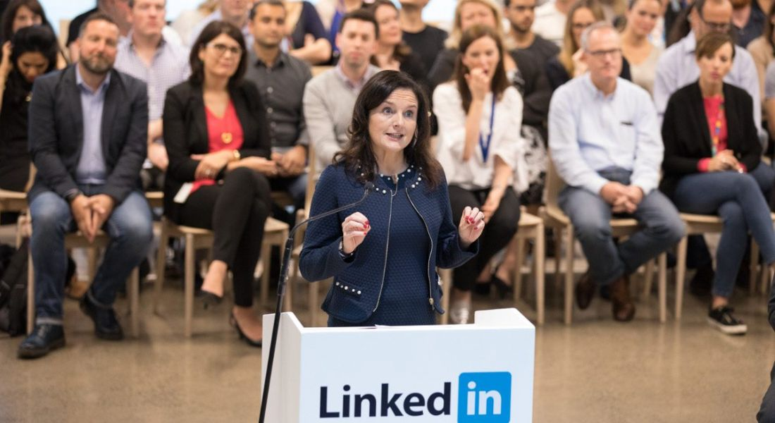 View of woman in navy professional business dress standing at LinkedIn platform announcing loads of jobs.