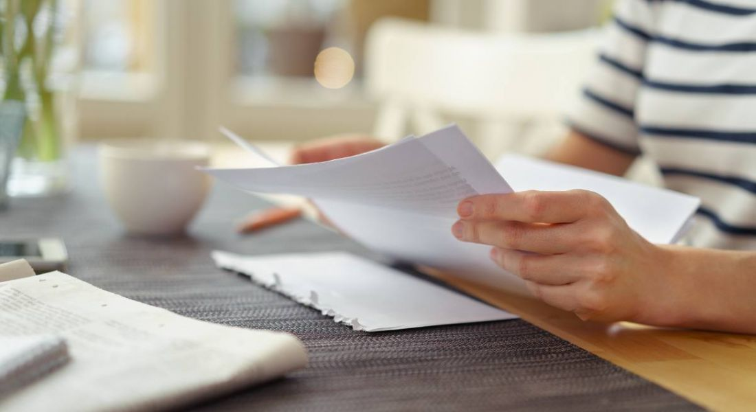 Close-up view of hands holding white paper on desk, reading over their cover letter.