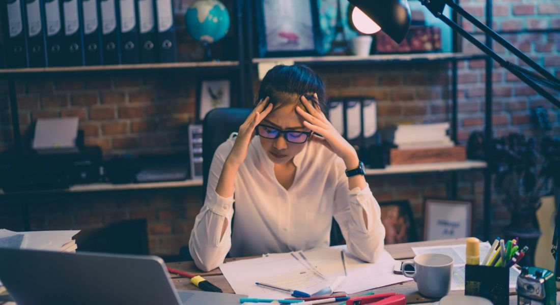 View of young woman in glasses with her hands on her head and brow furrowed with stress, poring over work.