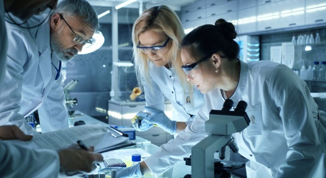 Three scientists, one man and two women, in a laboratory with microscopes and other research equipment.