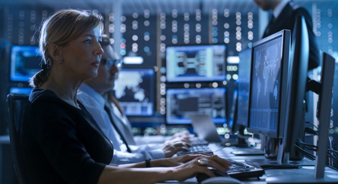 A cybersecurity professional in dark room typing away on her keyboard looking at dual screen computer set up.