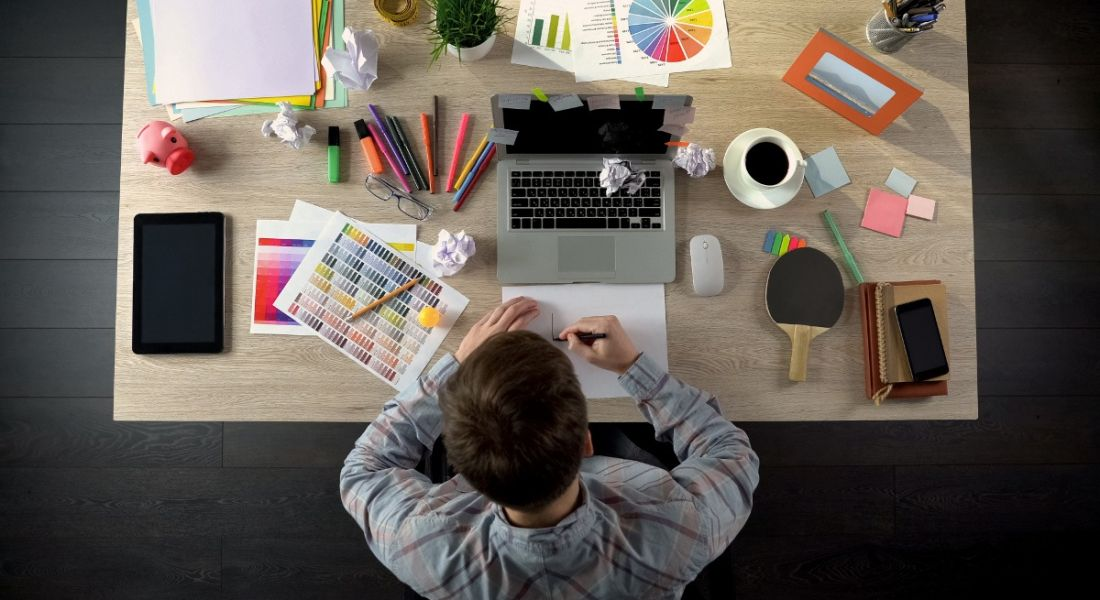 View of a man at a desk at work on his laptop. Desk is strewn with colour palettes and highlighters, showing he's using his creativity.