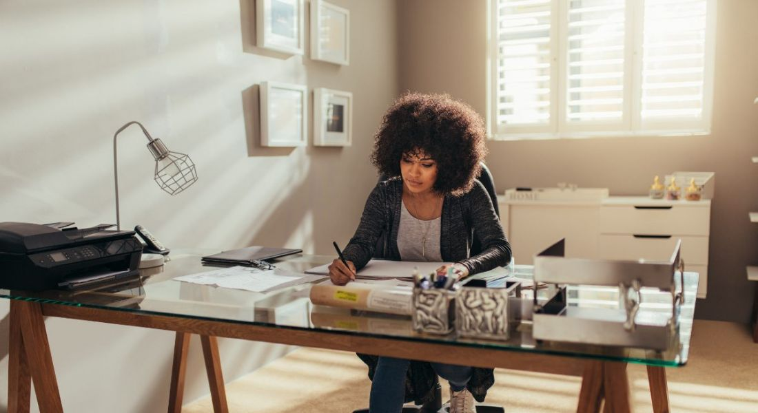 Woman sitting at desk in living room with plush carpet doing work and holding a pen.