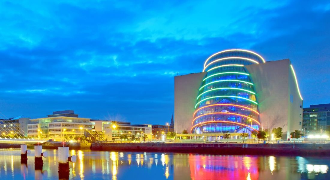 View of Dublin city convention centre and financial district illuminated at night.