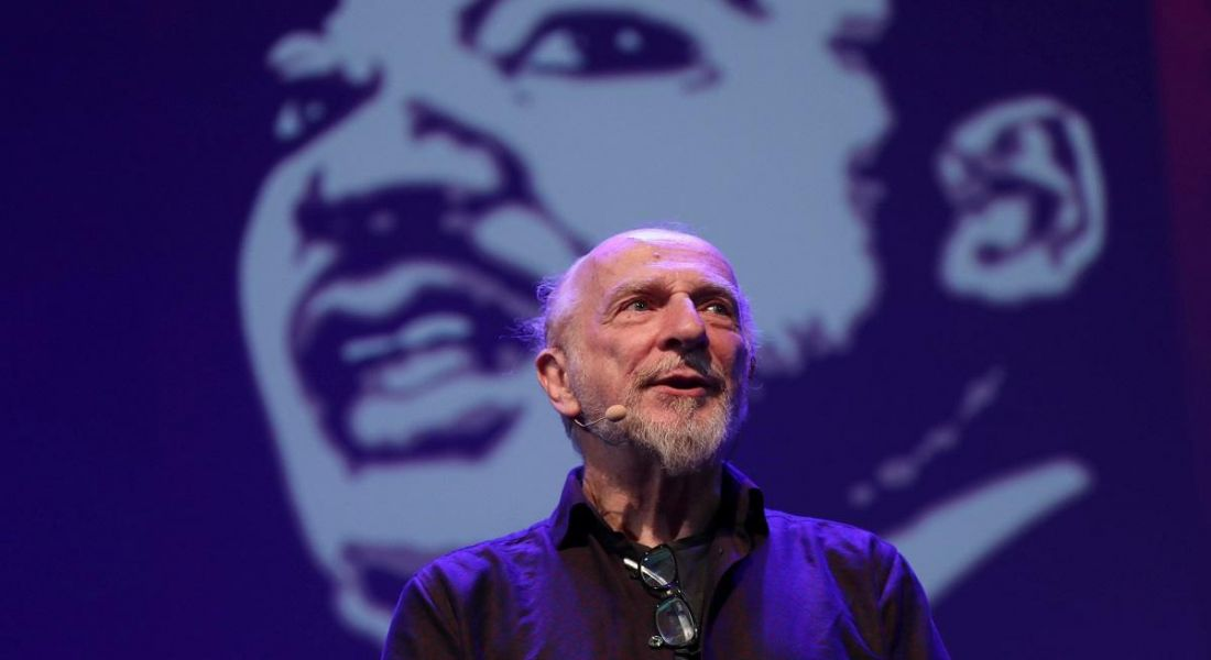 Jim Fitzpatrick in a black jacket standing in front of a projected image of his drawing of Martin Luther King Jr.