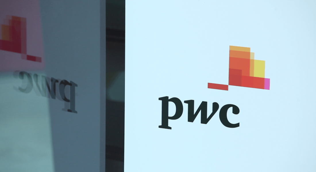 View of PwC logo on white wall reflected off nearby window.