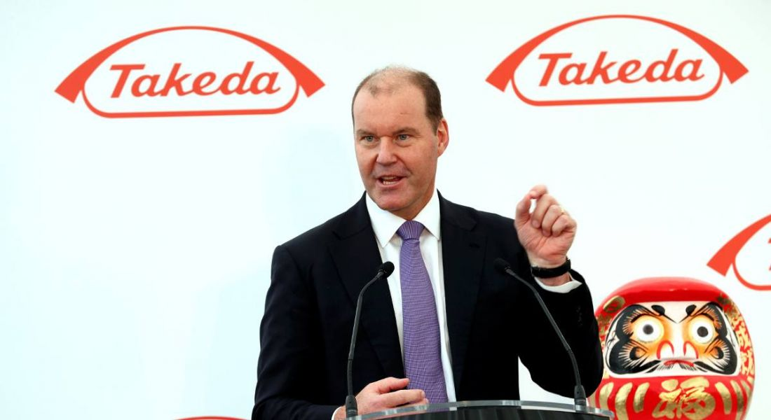 View of man in business suit standing at podium giving speech against backdrop emblazoned with Takeda logo.