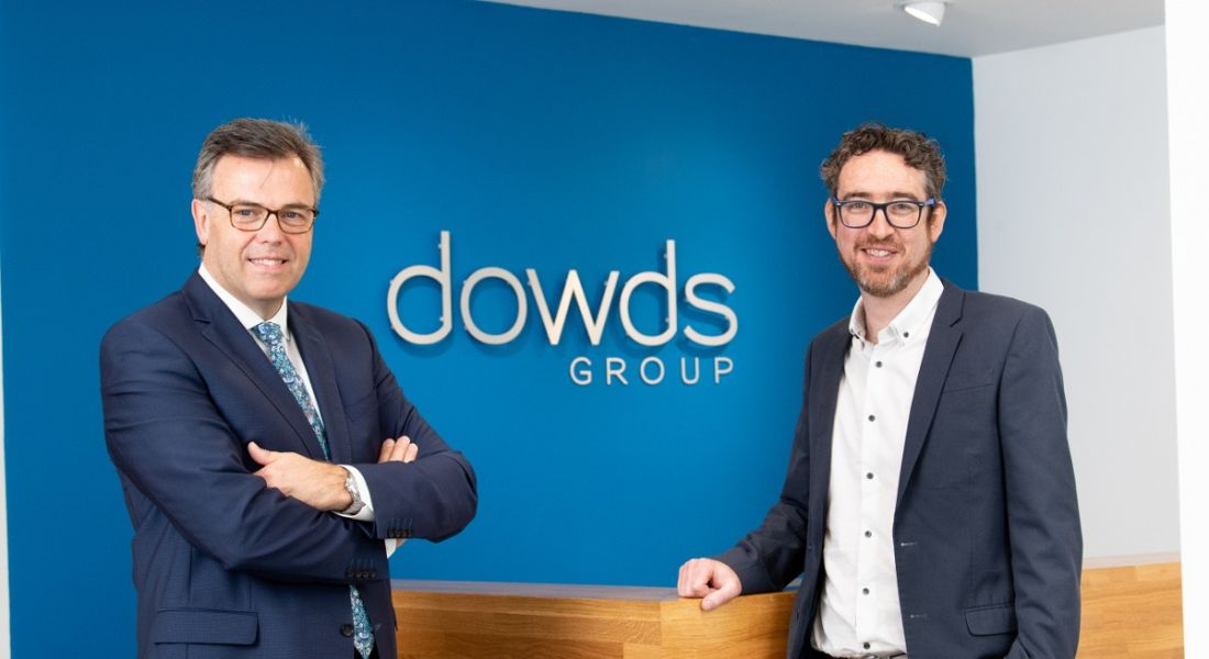 View of two men in business suits, one slate grey and one navy, standing in front of a blue wall with Dowds Group logo on it.