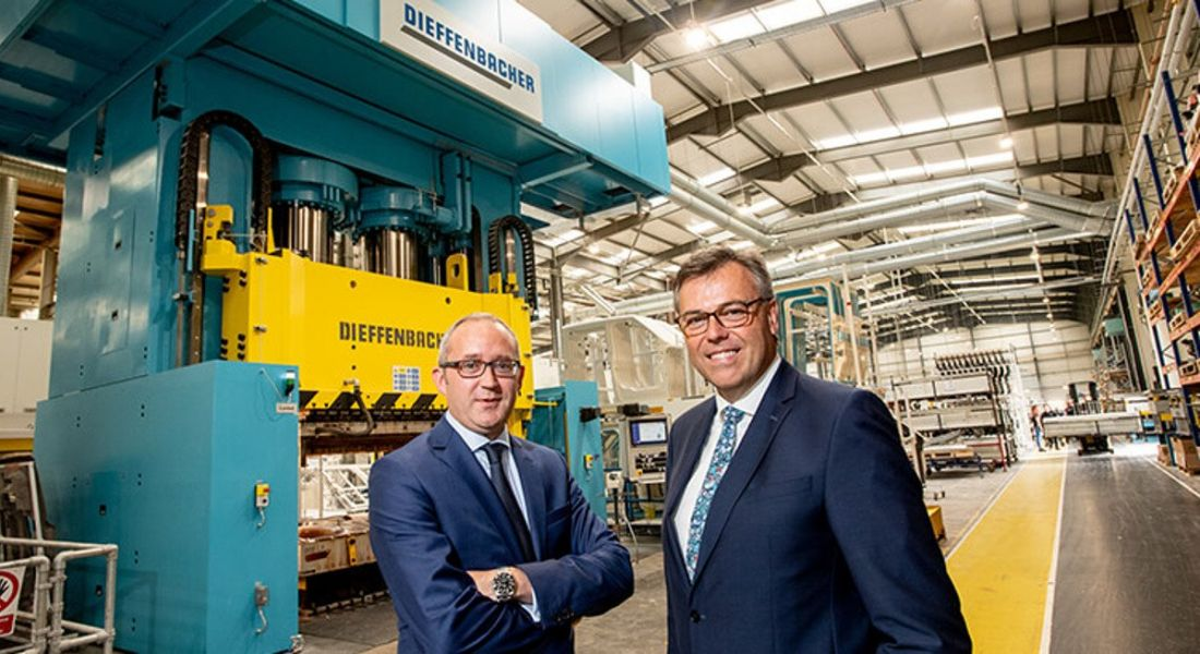 View of two men in business suits standing in manufacturing facility beaming at the camera.