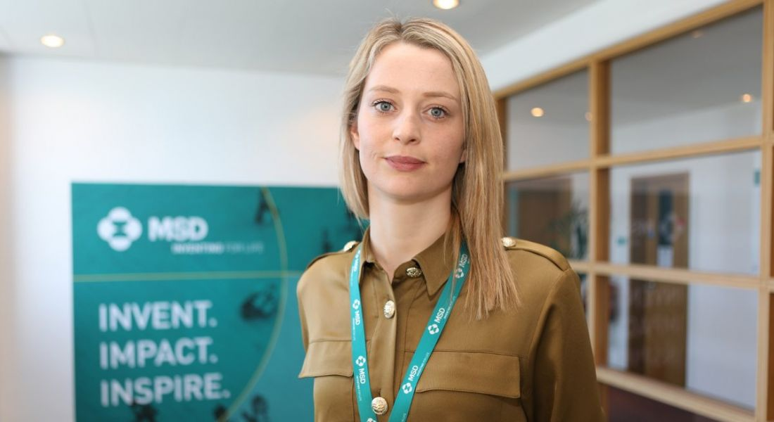 Young blonde woman with brown shirt wearing turquoise lanyard standing in front of MSD banner.