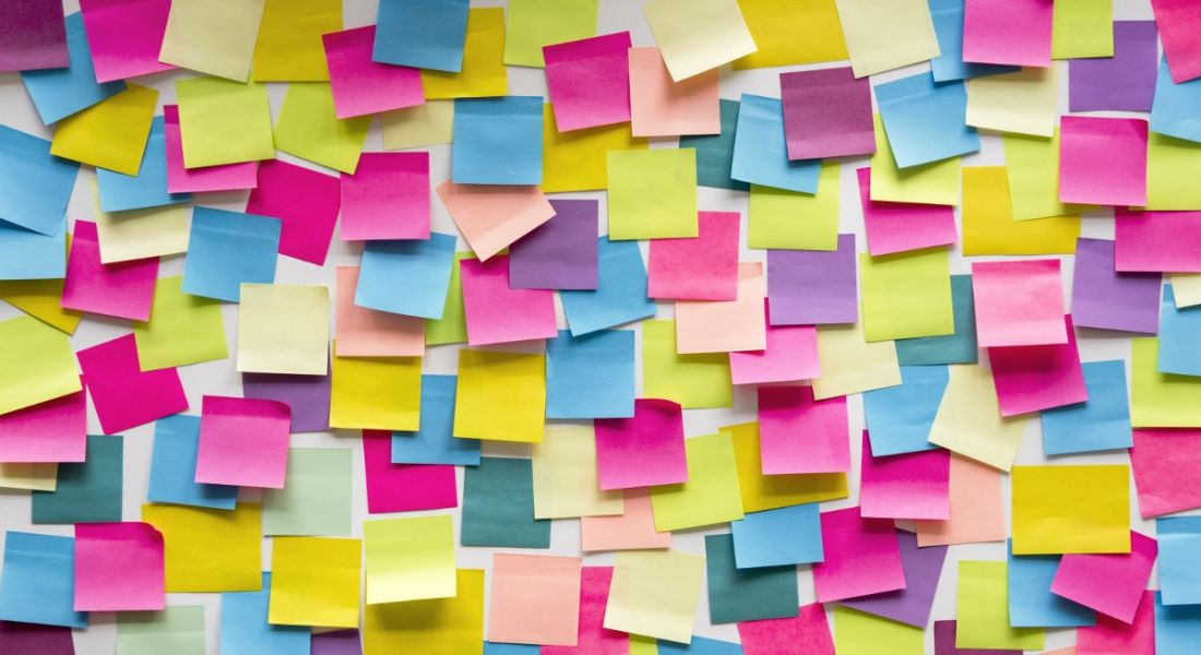 Multi-coloured sticky notes piled on top of each other on wall representing task debt concept.