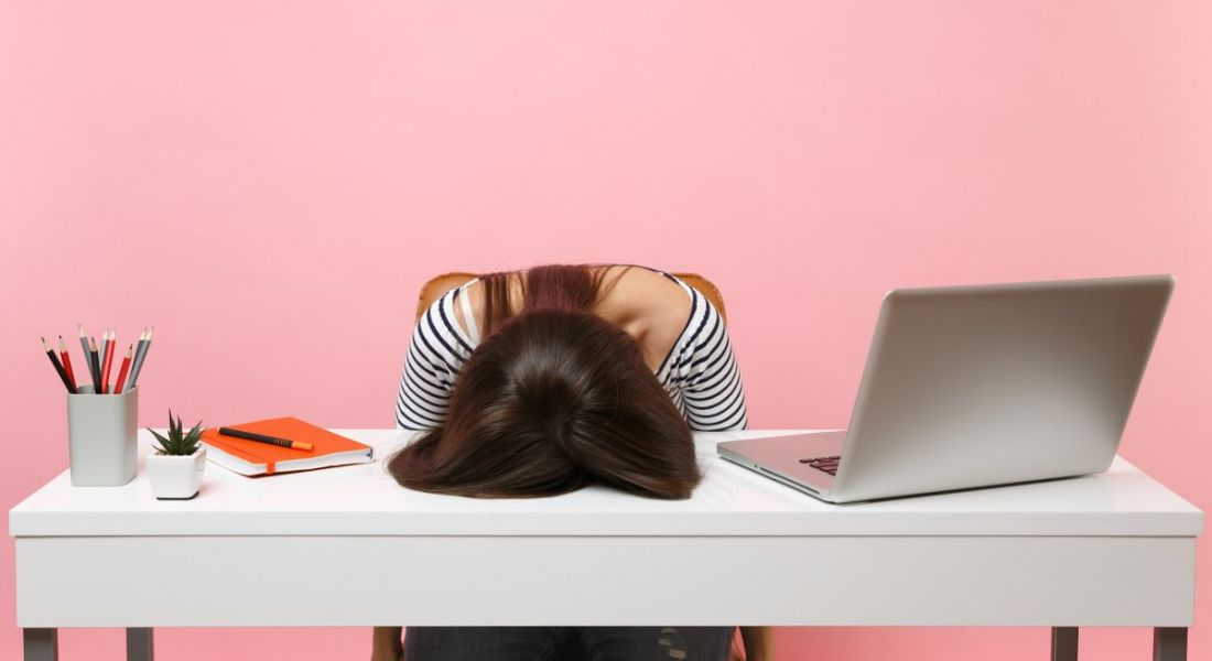 View of woman at work desk with head on the table experiencing burnout against bubblegum pink background.