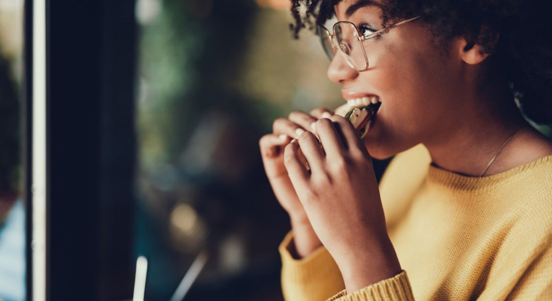 View of young woman with glasses smiling and biting into a sandwich on her lunch break.