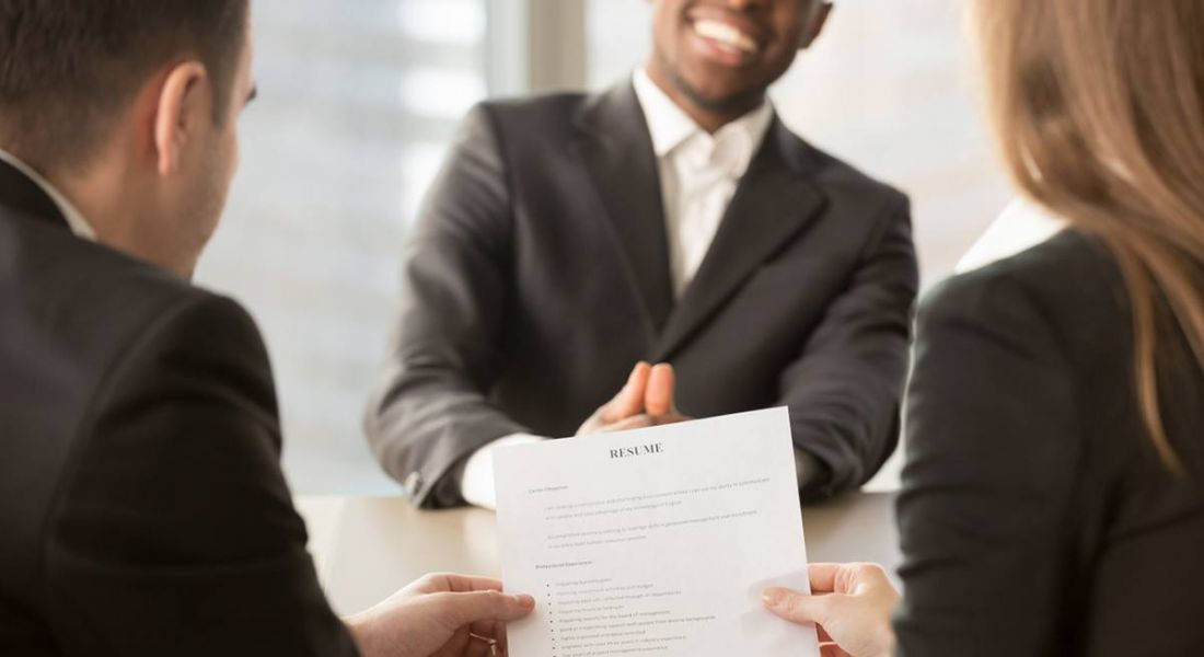 Employers review CV of confident job applicant smiling across table.