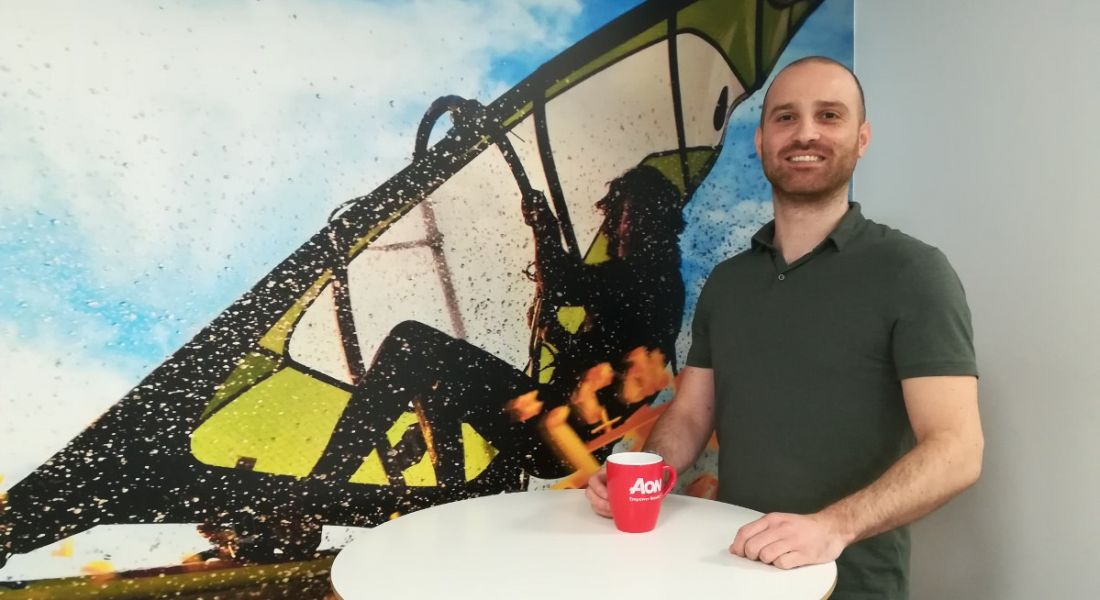 Young man in green T-shirt holding Aon mug and smiling against graphic mural background.