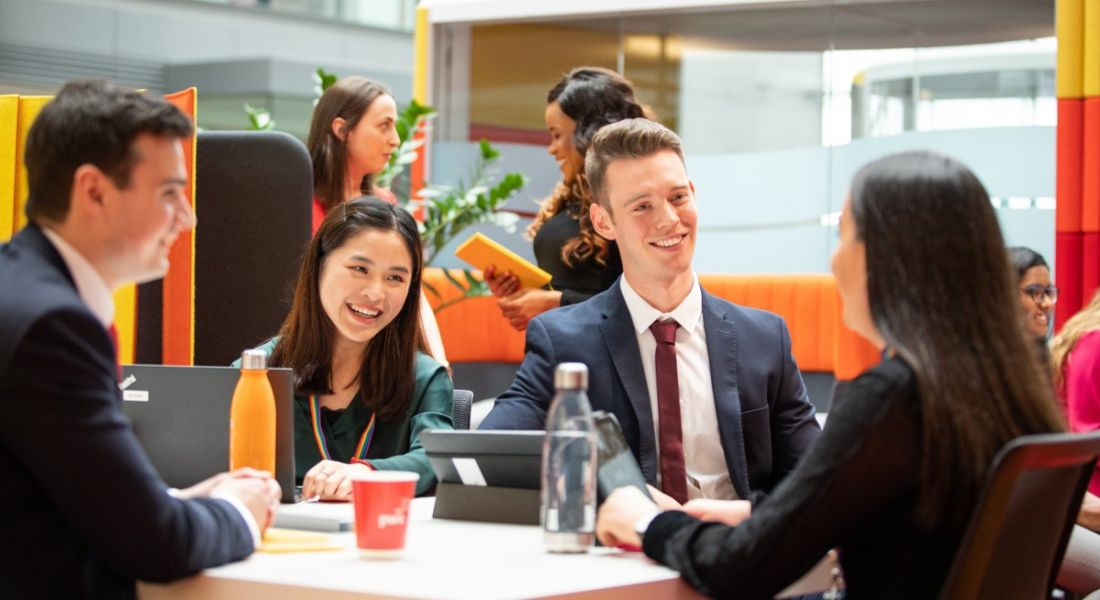 A group of young employees in business attire are sitting at a table and talking animatedly to each other.