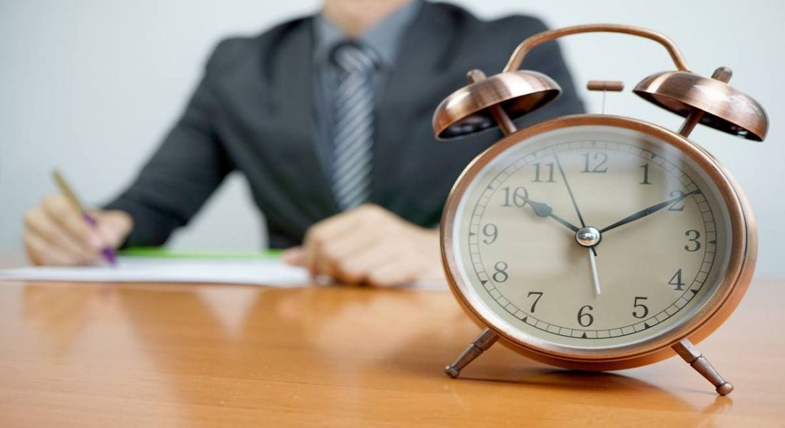 A businessman in a suit sitting at a desk behind an alarm clock with is the focus of the photo.