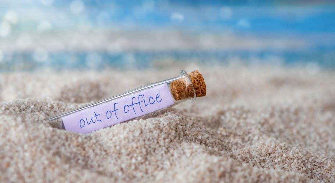 A sandy beach in a sunny location with a small glass bottle and a note inside reading 'out of office'.