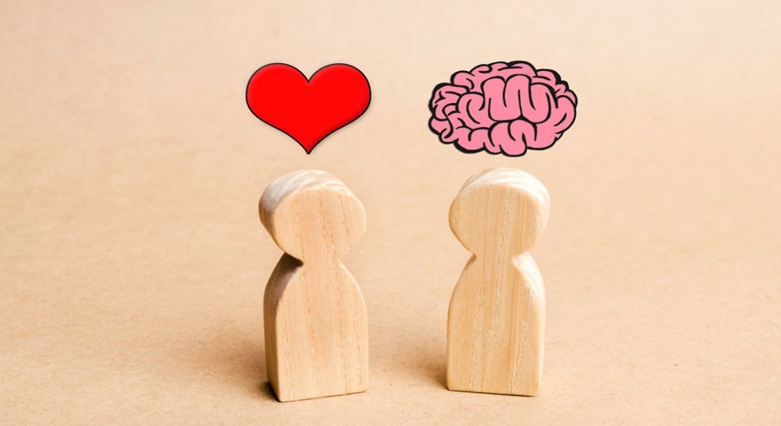 Wooden figures on a table, one has a cartoon heart above its head and the other has a cartoon brain above its head.