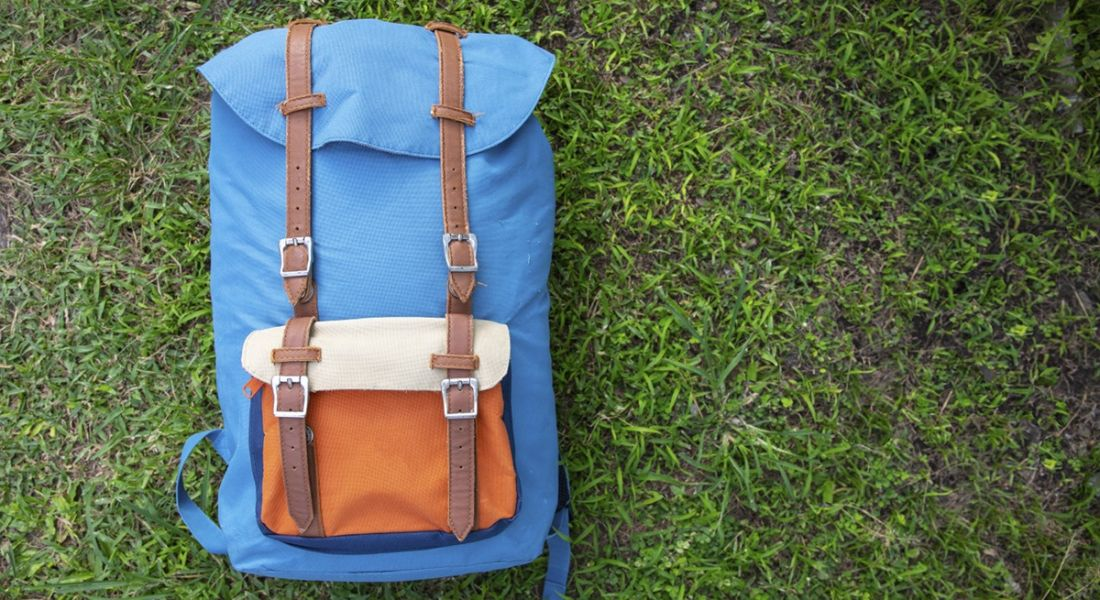 A blue and orange rucksack laid down on grass.