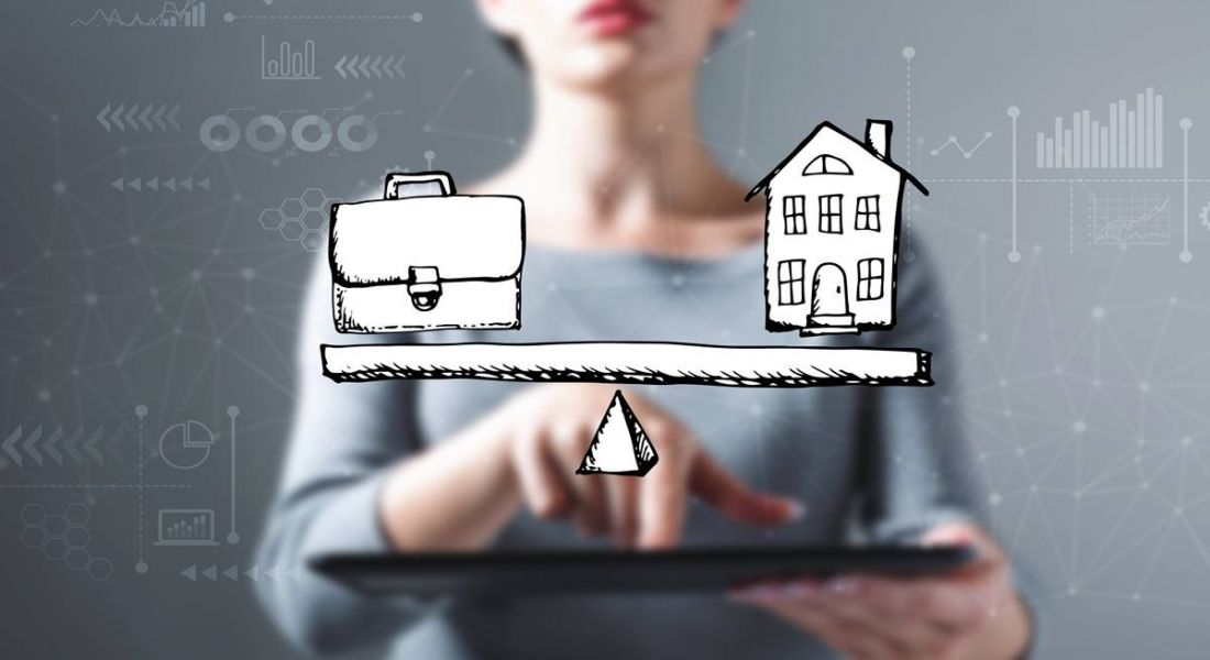 Woman is standing in front of a grey background and behind an illustration of a scale with a briefcase on the left and a house on the right.