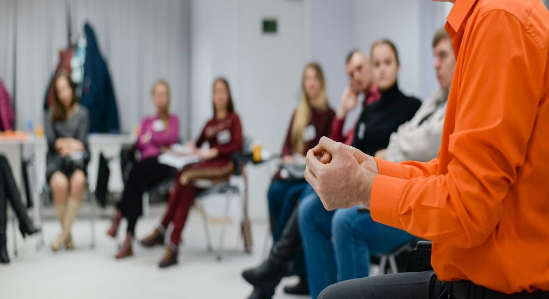 Lecturer conducts a lecture, training older workers with professional development, standing in a circle of people sitting and listening in a classroom setting.